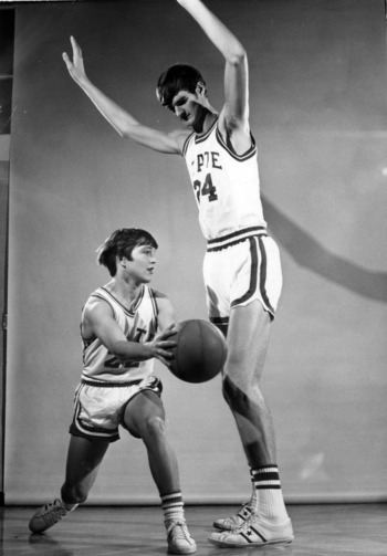 "Monte Towe at 5'7"" posed against an average high basketball player"