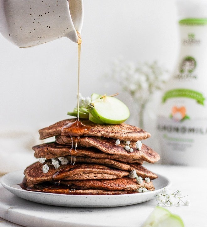 A tall pile of plant-based pancakes with a bottle of almond milk in the background