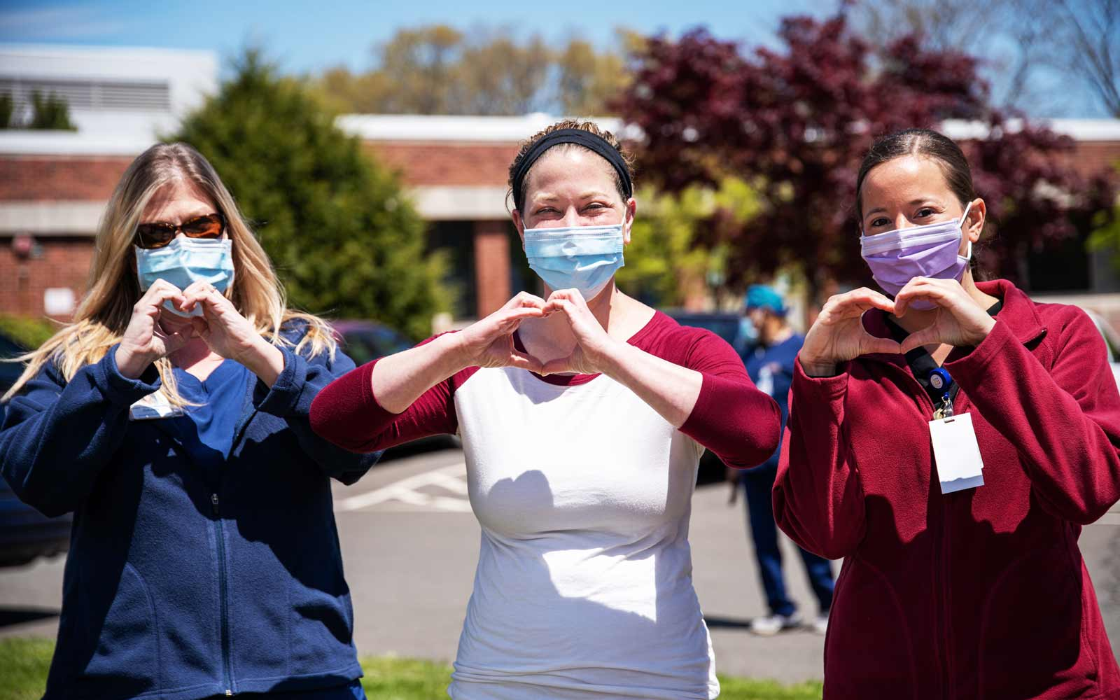Three women wearing masks making hearts with their hands.
