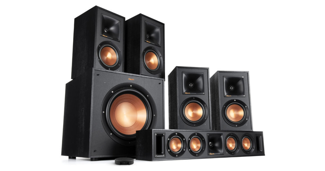 The Platin Monaco 5.1 wireless audio system features a subwoofer, center channel speaker, Axiim LINK wireless USB transmitter, two front satellite speakers, and two rear satellite speakers. Components are compact, and have a black finish.