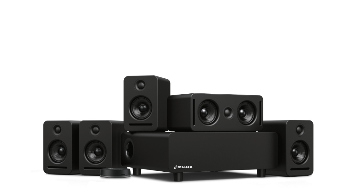 The Platin Monaco 5.1 wireless audio system features a subwoofer, center channel speaker, wireless audio transmitter, two front satellite speakers, and two rear satellite speakers. Components are compact, and have a black finish.
