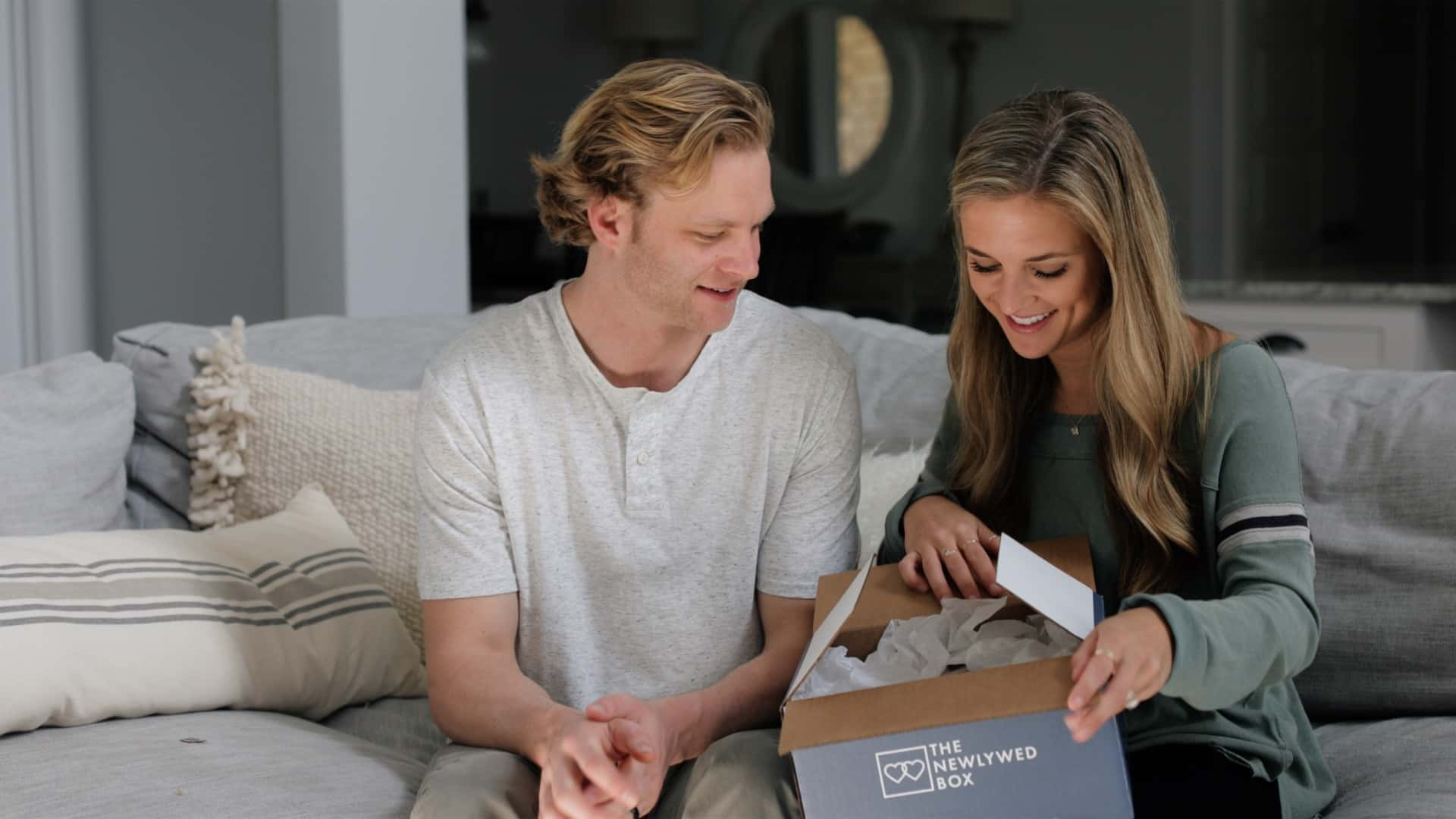 "A young couple owns a box reading ""The Newlywed Box"" on the side."