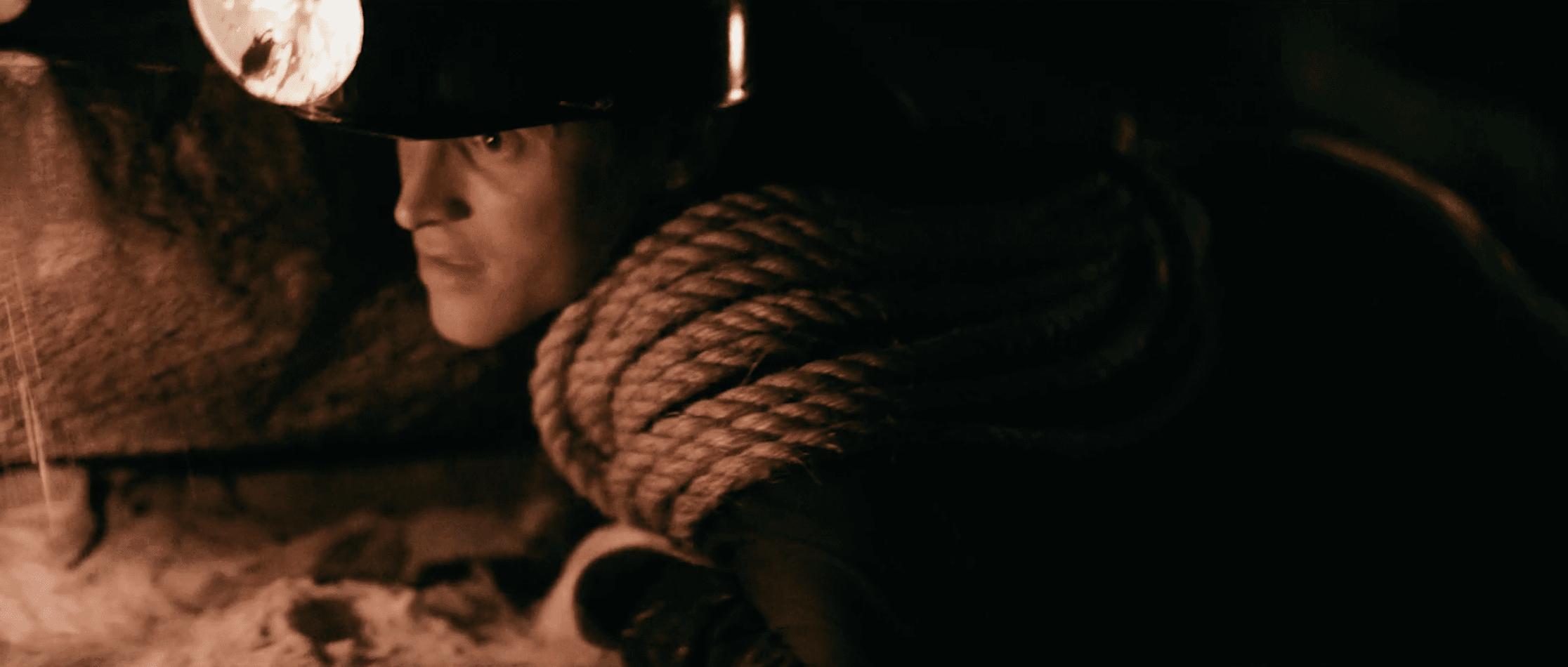 A man crawls through a cave wearing a vintage head lamp.