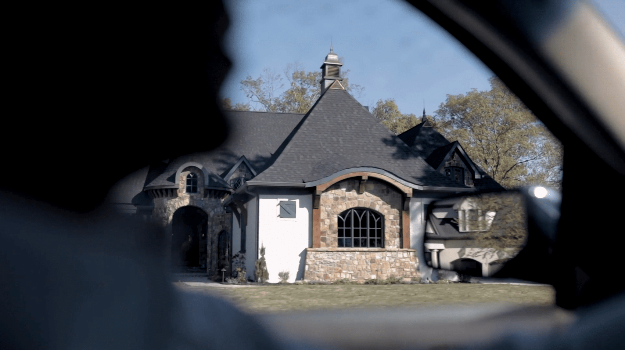 Shot of the front of a home as seen from inside a car as it drives by.