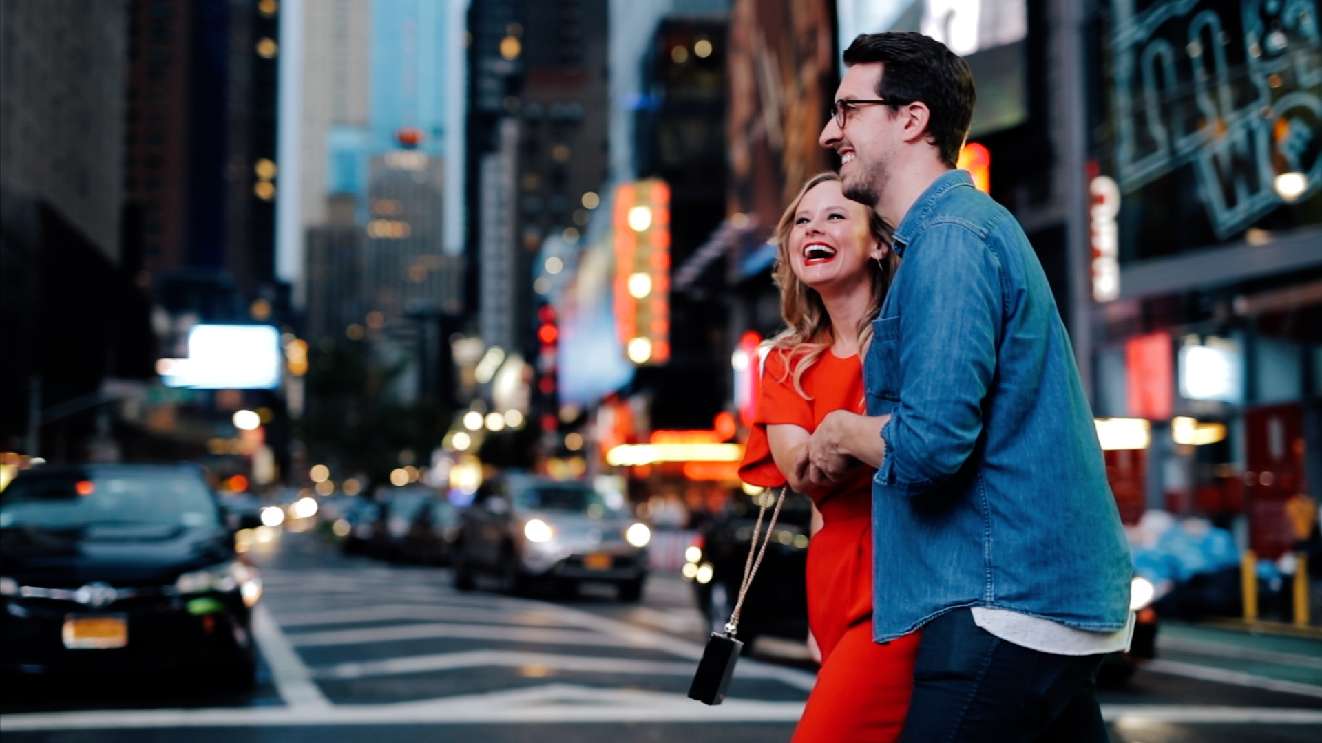 A couple walks happily down Broadway in New York City