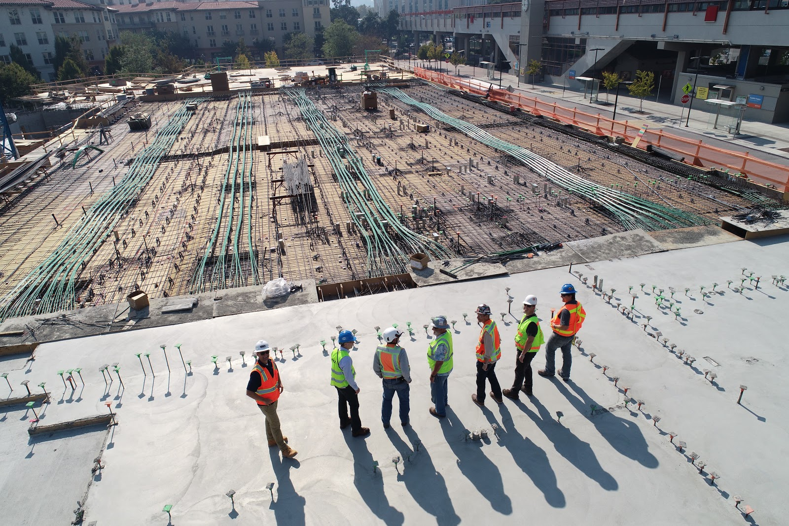 Seven construction workers on an electrical construction site standing in a row.