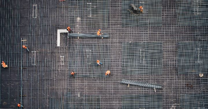 Aerial view of construction workers building a skeleton frame with steel columns.