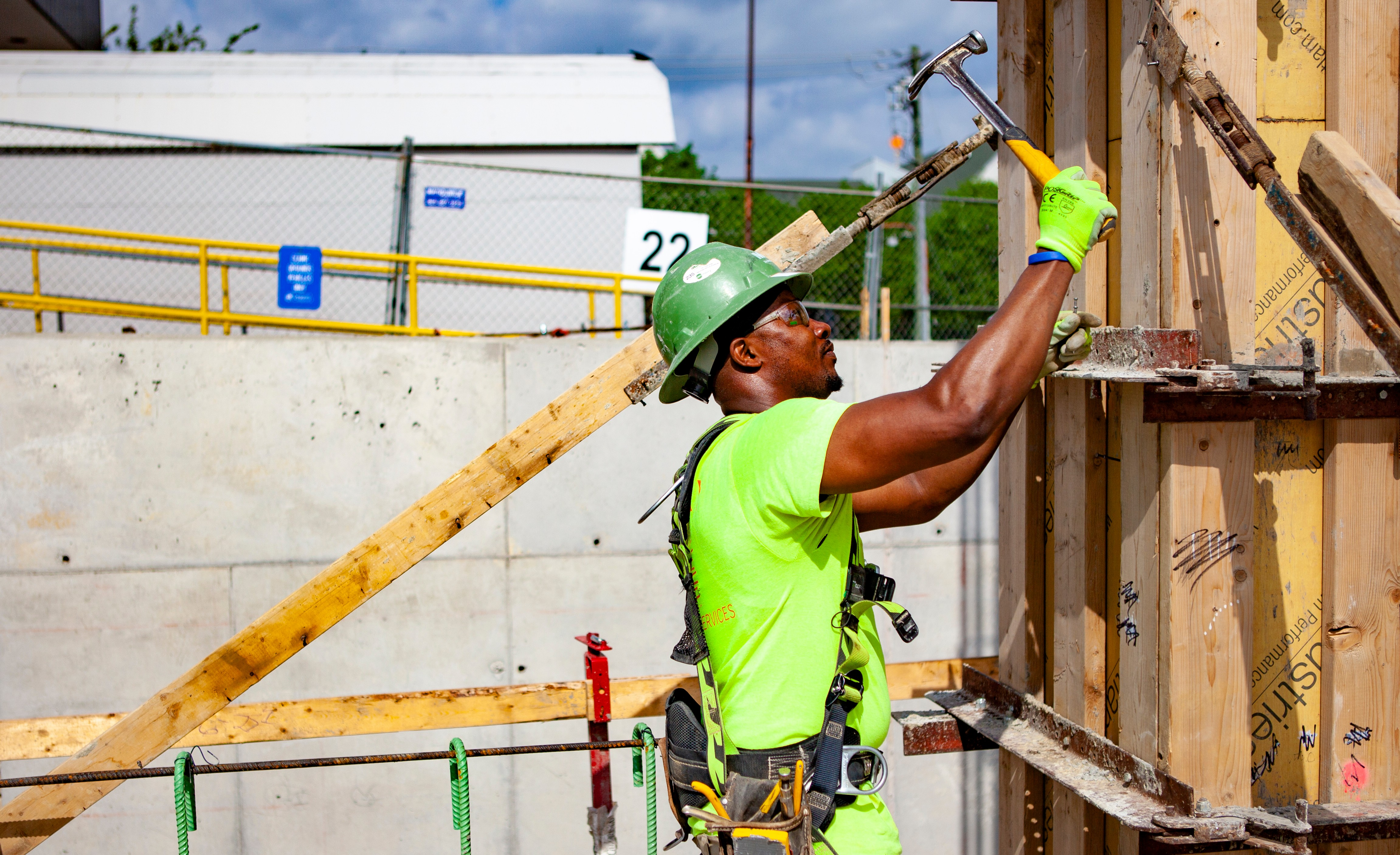 One construction worker hammering a board at a construction site.