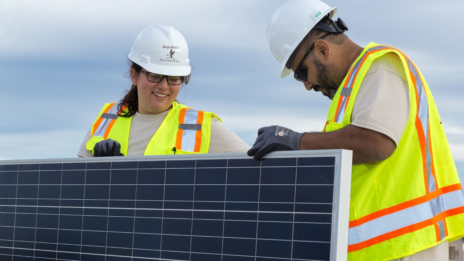Two Sprig Electric construction workers working together on a solar panel.