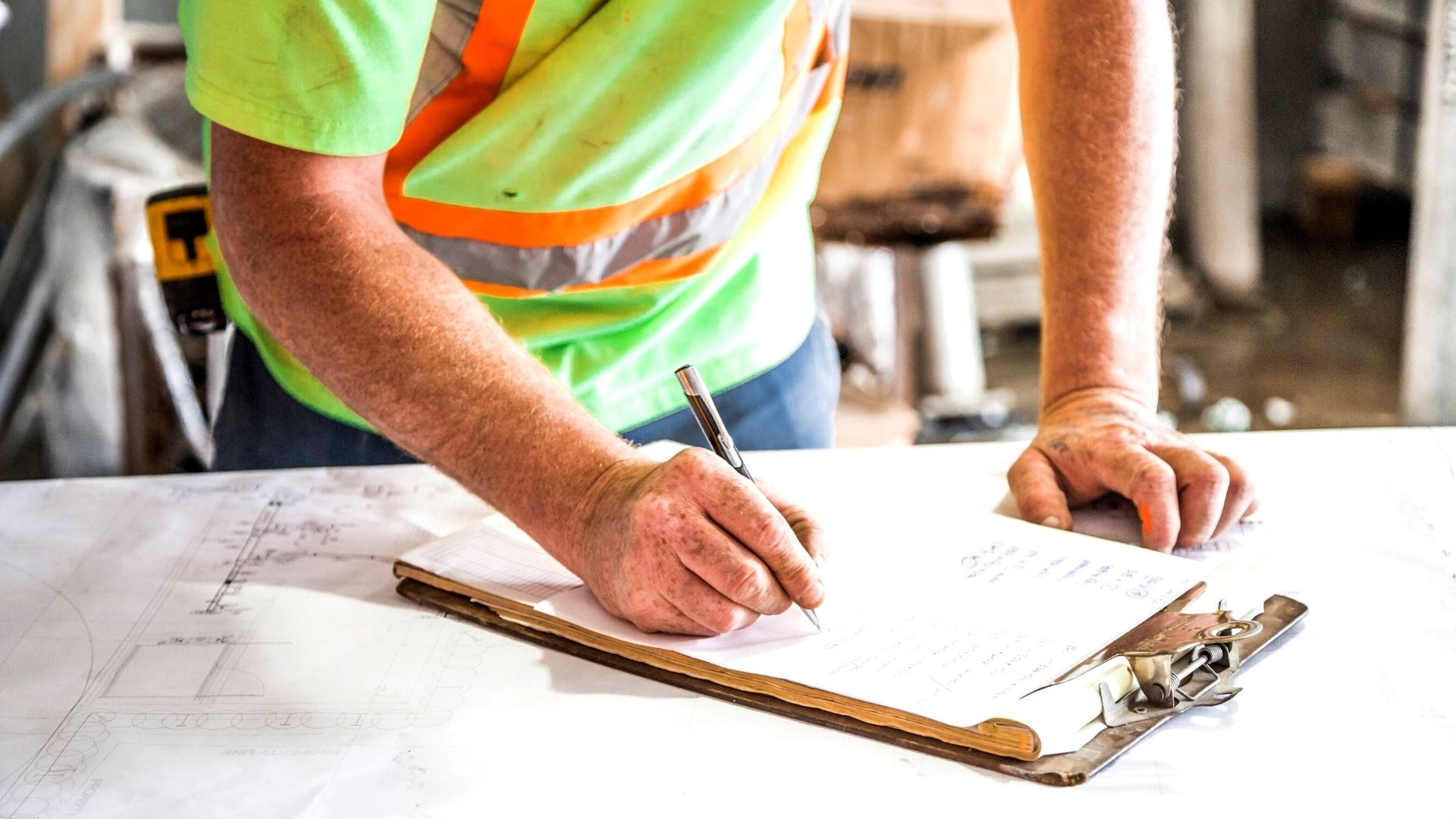Construction worker writing on a clipboard that is on a white table.