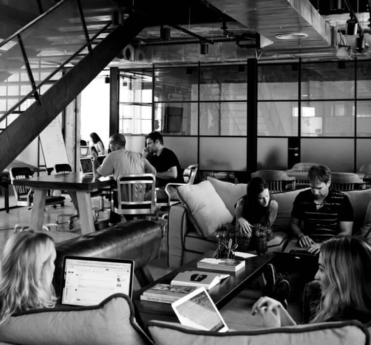 startups sitting in a co-working space. 2 people on the couch. 2 people at a table below a staircase.