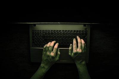 hacker hacking a server in the dark. the light from the screen makes the hacker's hands visible.