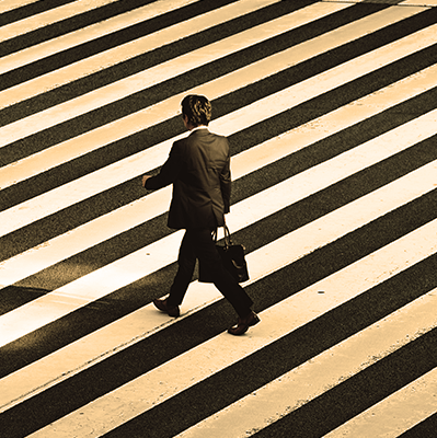 Man in black formal suit jacket and pants carrying black bag while crossing and empty crosswalk.