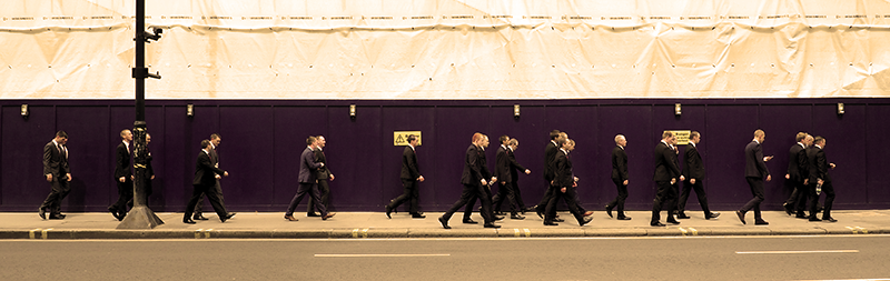 25 Londoners suited up and walking on the sidewalk in front of a building site.