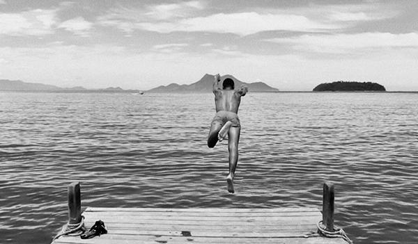 young man jumping off a dock at a lake.