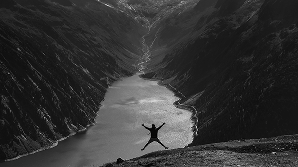 man jumping for joy like a starfish in front of a lake tucked away in the austrian mountains.