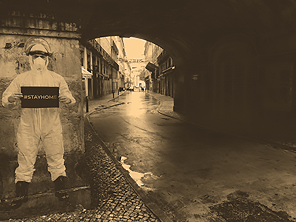 sepia photo of a man walking under a tunnel in lisbon, portugal during the coronavirus pandemic.