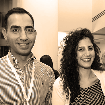 headshot of two well-dressed young entrepreneurs. the smiling man is where a button-up shirt. the curly-haired, energetic woman is