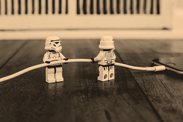 two lego stormtroopers plugging in a charger cord into an iphone.