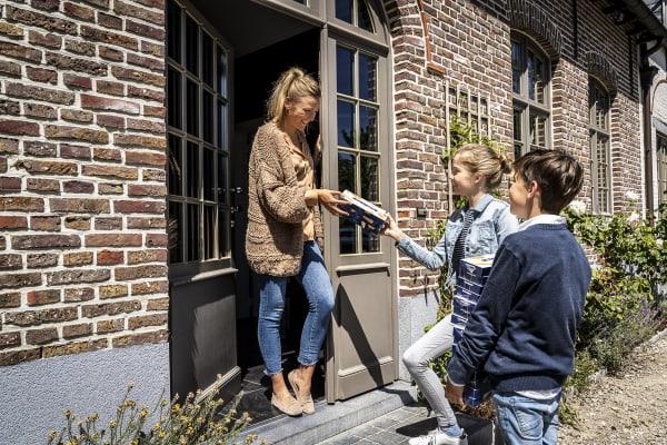 Kinderen verkopen Jules Destrooper  koekjes deur aan deur