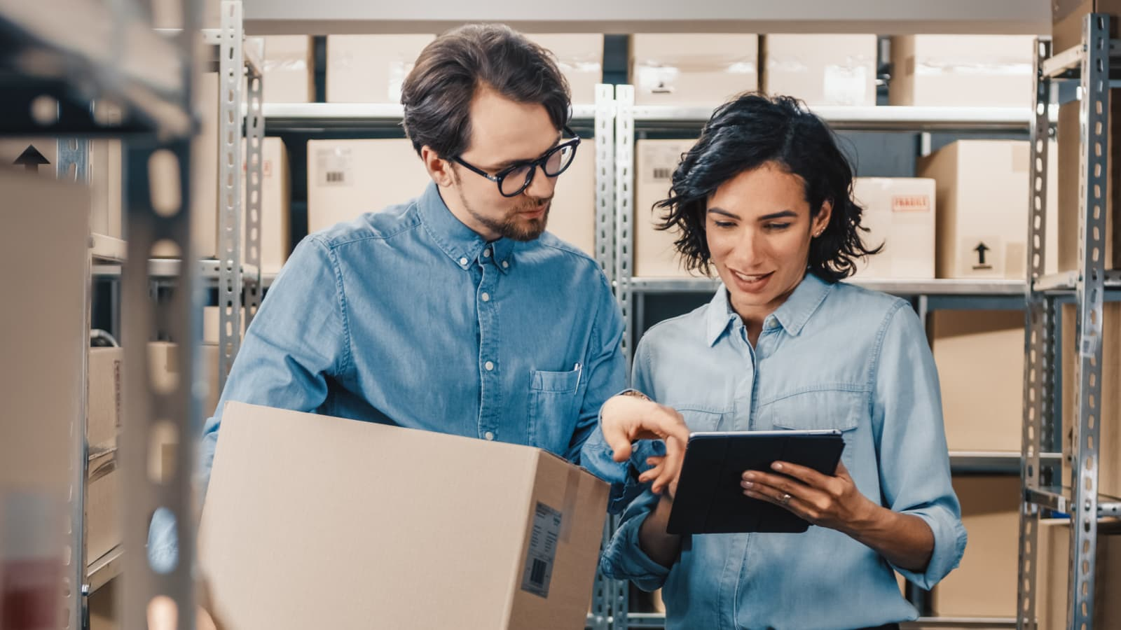 Recall InfoLink two people in warehouse looking at a tablet.
