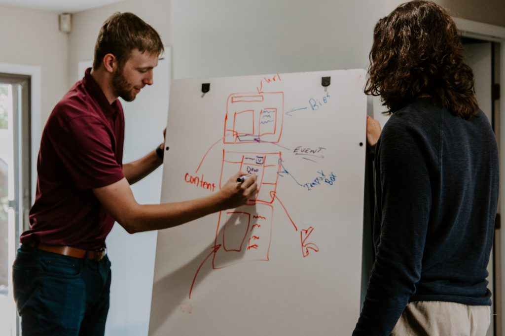 Man and women holding a discussion with a whiteboard