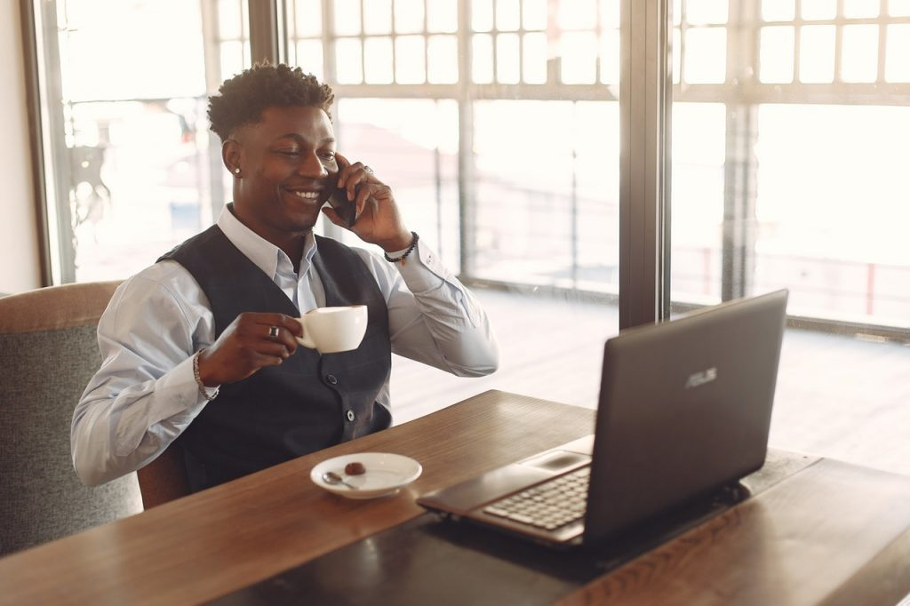 man drinking coffee and answering call