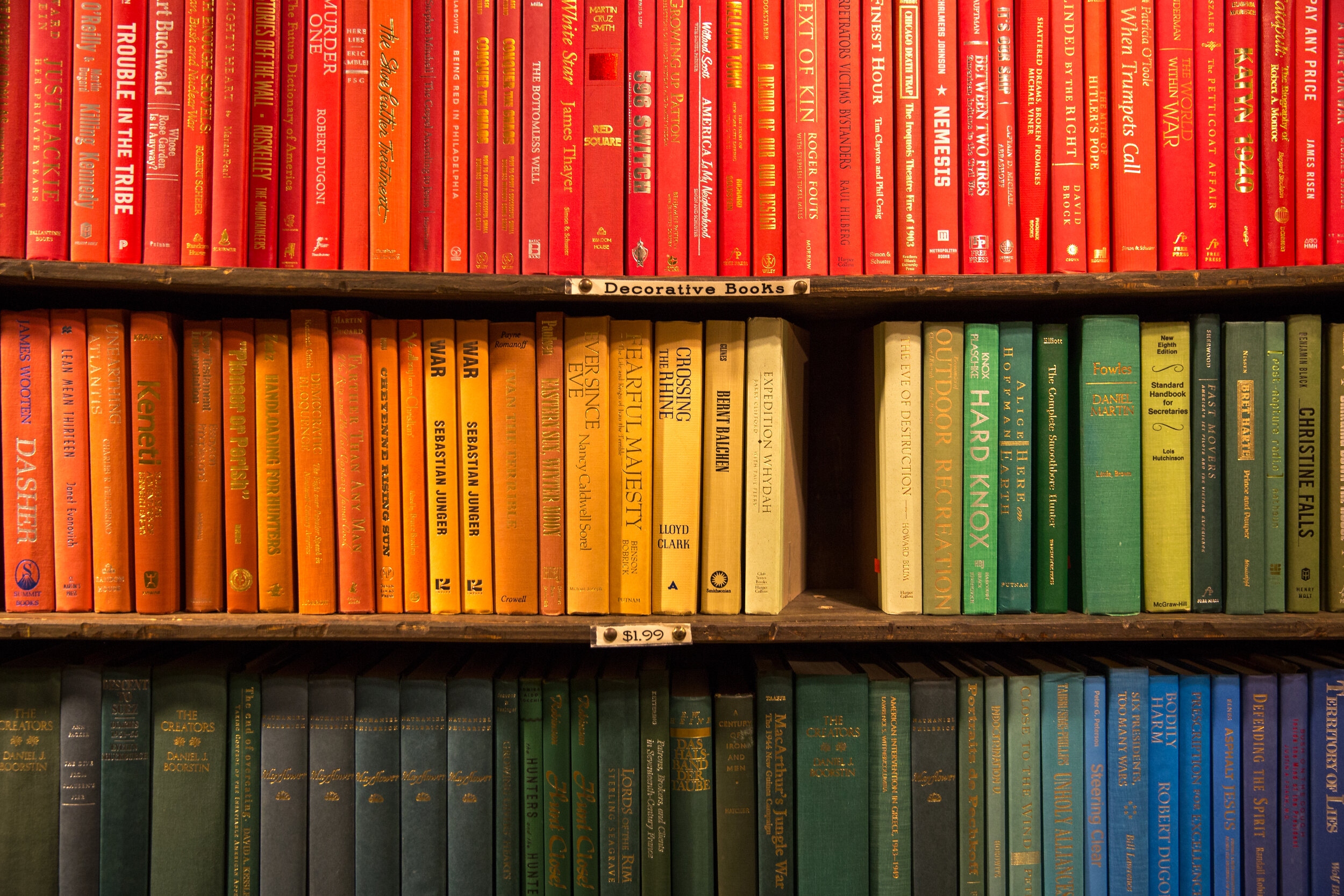 By Color   This is perhaps one of the best ways to organize your books if you are looking to create a visual statement, though it can be one of the most exhausting to pull off. To effectively organize your bookshelf based on color, I recommend splitting books into color categories based on the color of their spine. Once you have your books paired into colors, take it a step further and group the books in that color category based on how dark or light the coloring is.  After you have divided the books into your color groups, display them on your shelves in descending order so that it creates kind of an ombre look. If you want your shelves to truly make an impact in your home decor, this is absolutely the way to display them!  However, it should be mentioned that if you elect to go the color organization route that you cannot choose to simultaneously organize them with a second method such as alphabetization. This will ruin how the colored spines are displayed. And though this might seem like it would be a hard way to go back and find an old book to read, if you can remember the cover, things are usually pretty easy to find! Plus, this organization method makes your shelves totally Instagrammable!