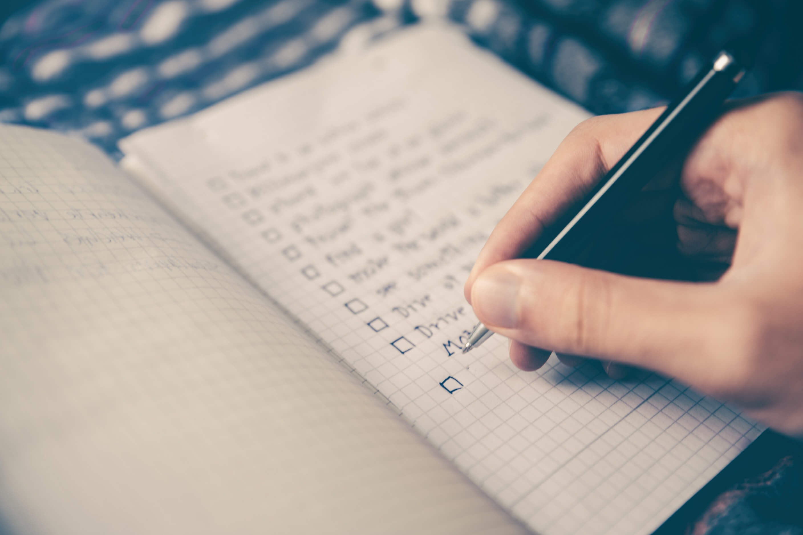 A person working on a checklist in a notebook with graph paper