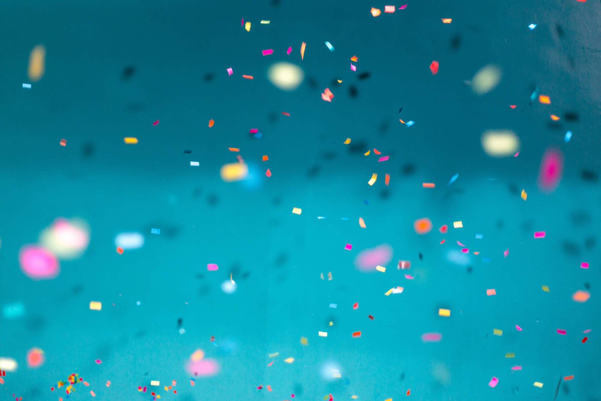 Colorful confetti falling against a teal backdrop