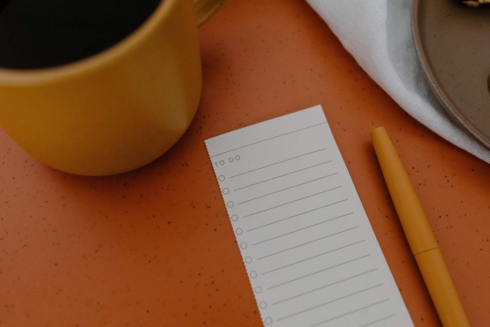 Orange coffee cup on an orange table with a to-do list and orange pen