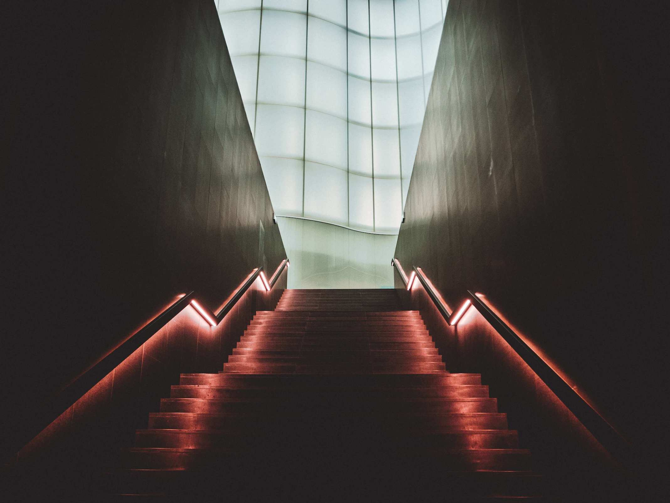A dark staircase lit with pastel pink lights leading to a gigantic window