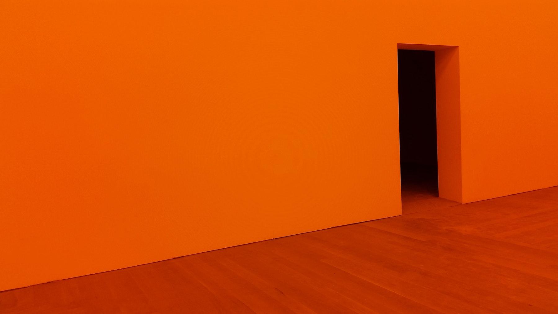 An orange room with a wood floor and on open doorway