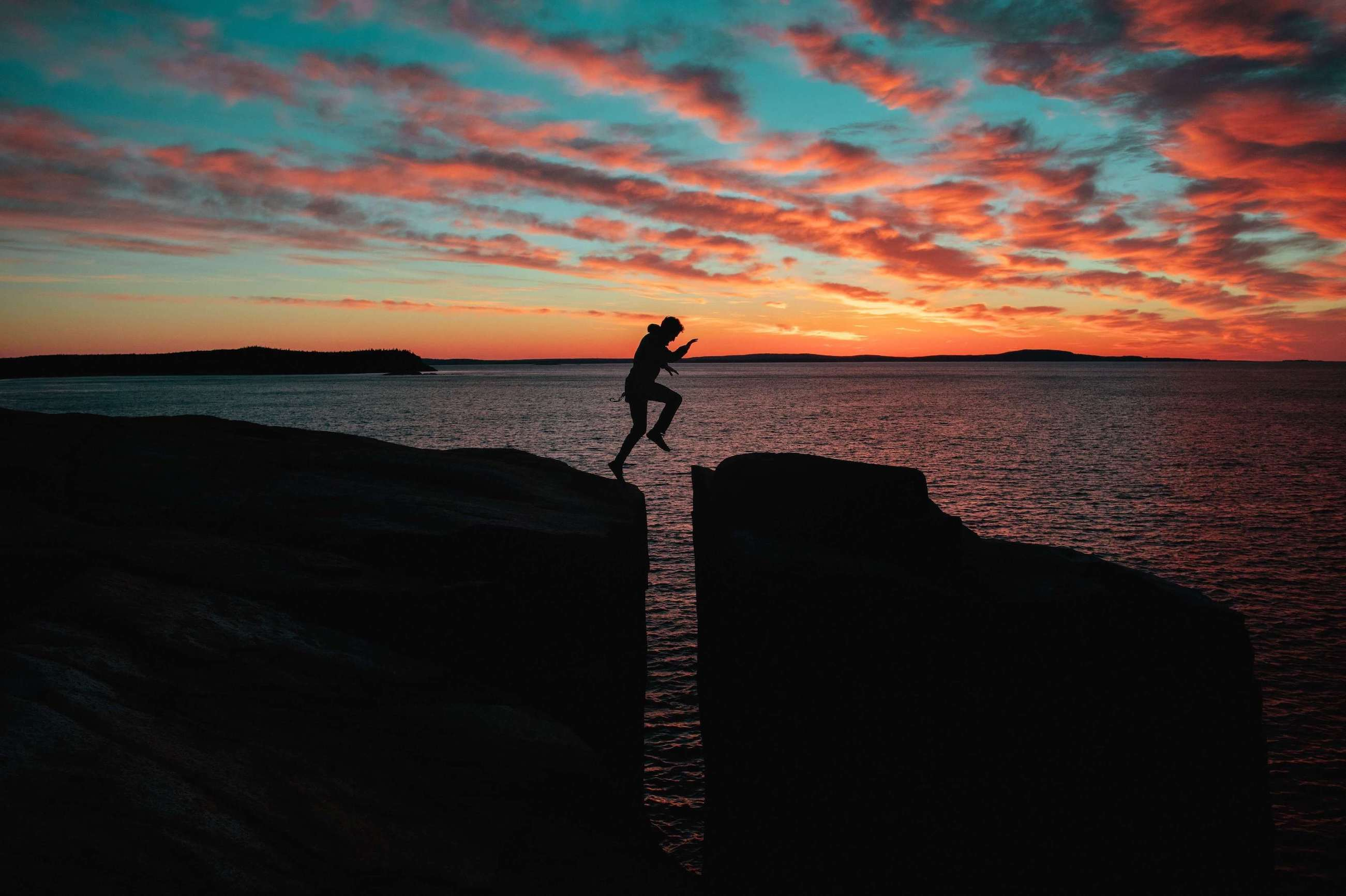 A man jumping across two rocks next to the sea during sunset
