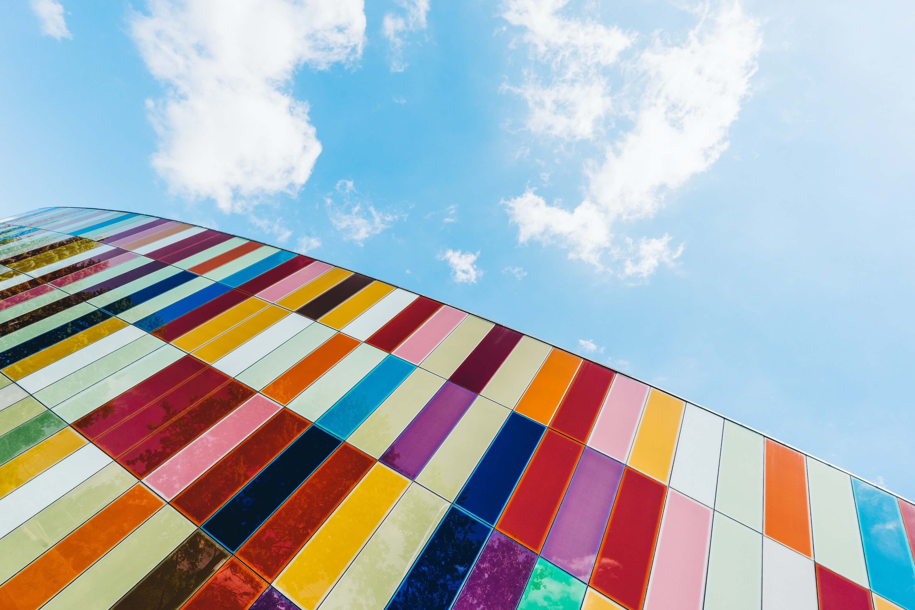 Blue sky behind a building with many colorful, rectangular tiles