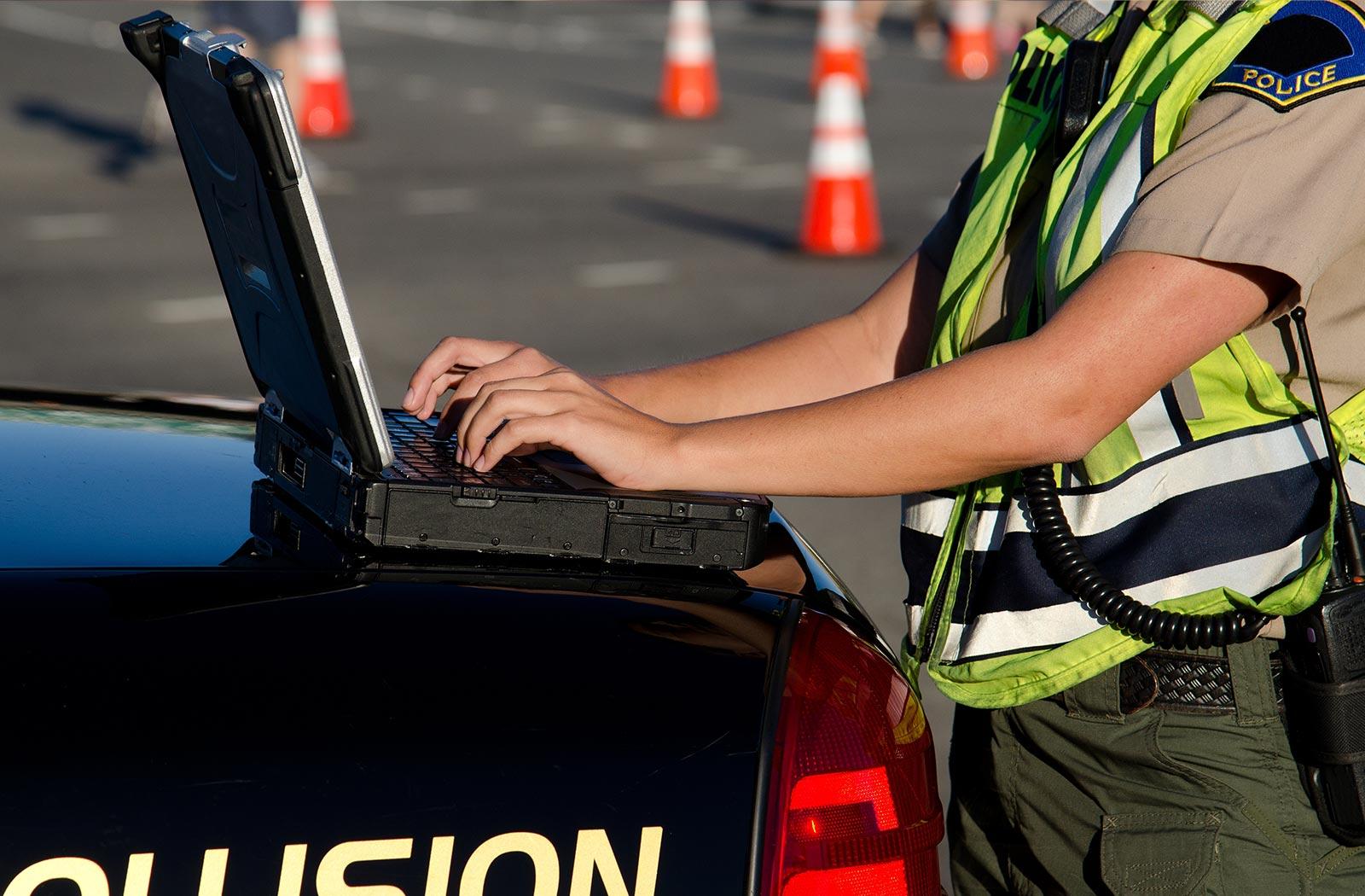 Un oficial de seguridad pública trabajando en un portátil que se apoya en un coche