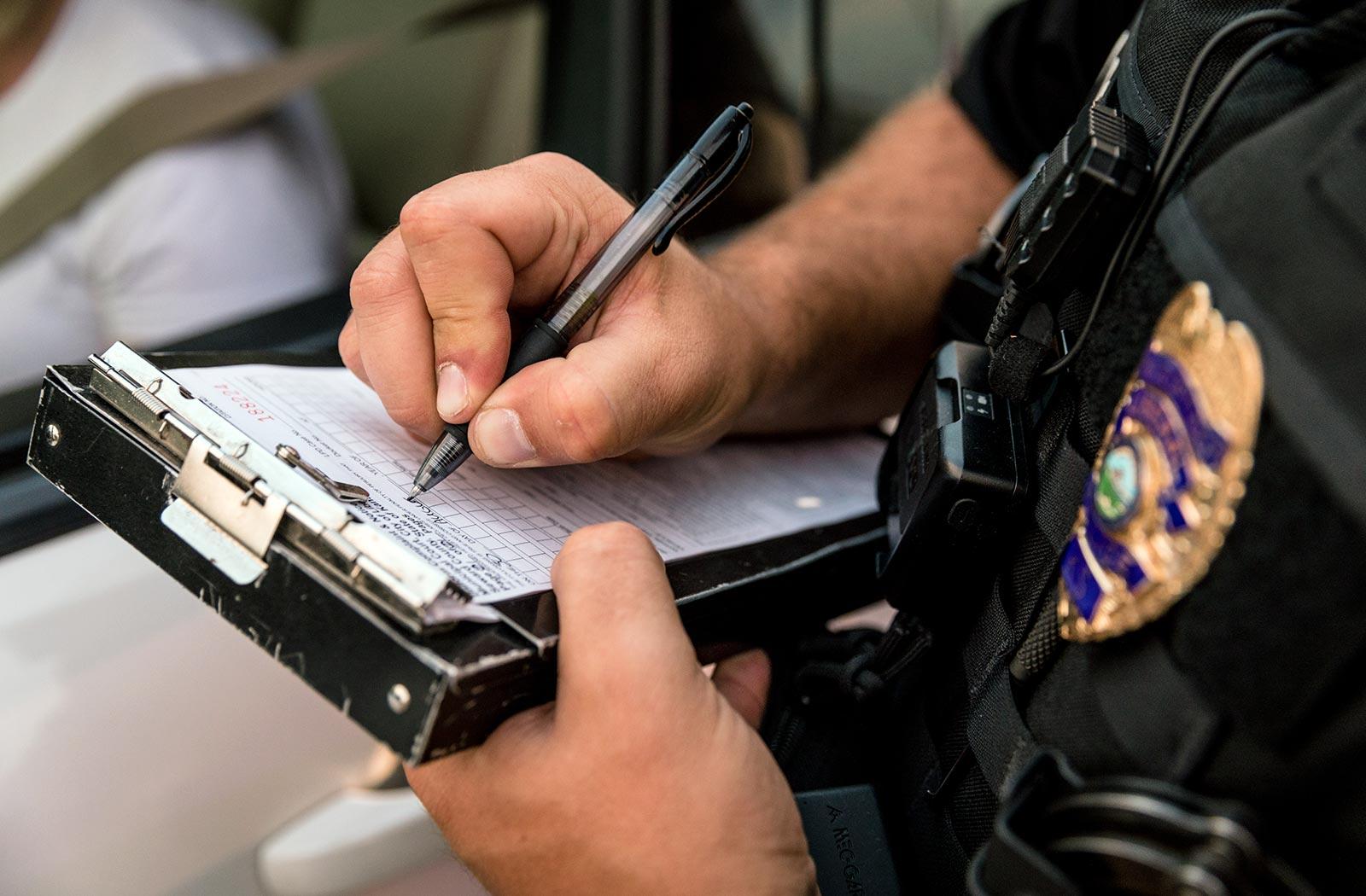 Un oficial de policía escribiendo información en un bloc