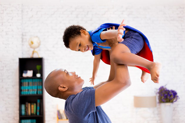 Man plays with son dressed as a super hero.