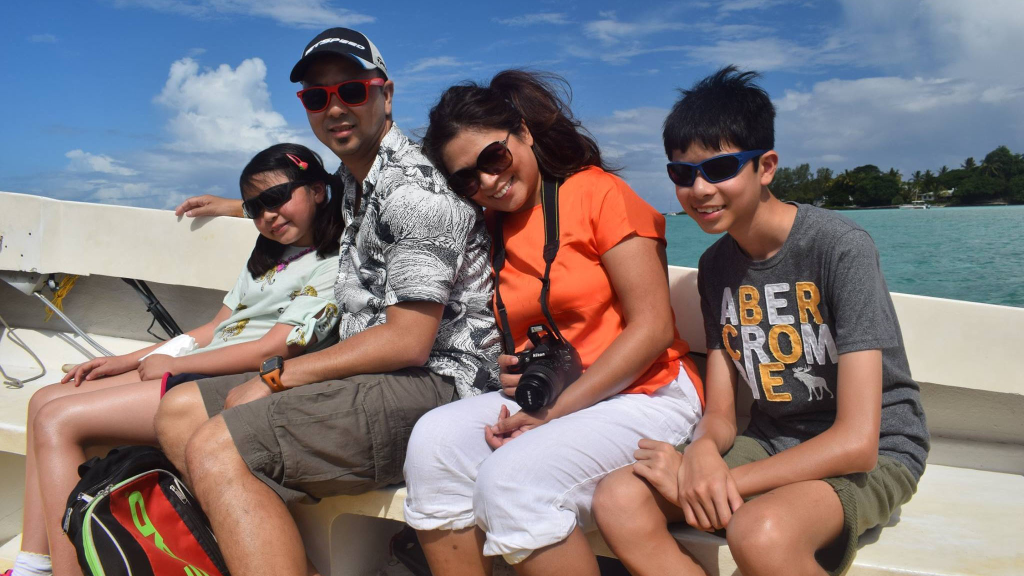 Engineer Sheila sits with her family on a boat.