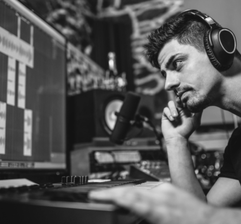 A producer paying attention to what he is creating on the computer.