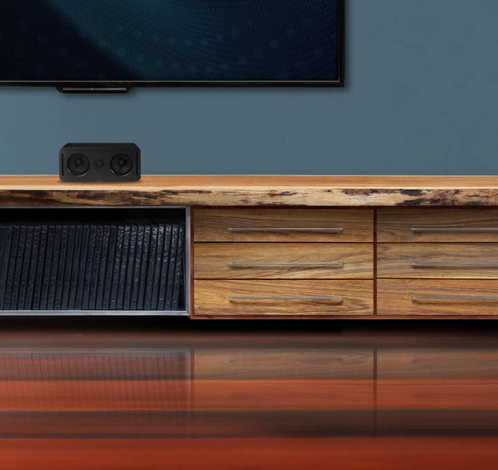 Two components of a Platin sound system are displayed on and under a low console-style table in a contemporary living room.