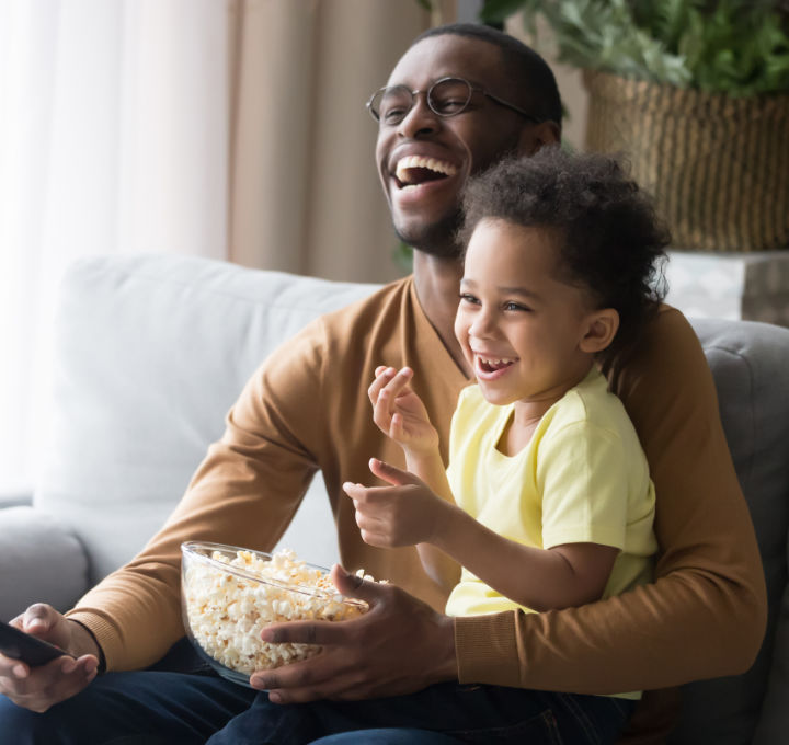 A laughing father and young son are sitting on a couch, eating popcorn, and watching TV together.