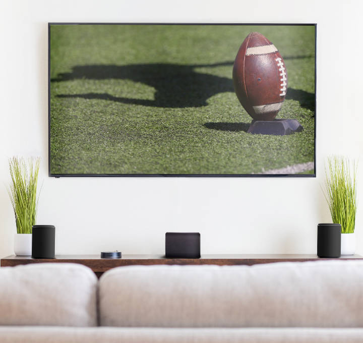 Contemporary living room with Milan speakers on a credenza; television has football game kickoff on the screen