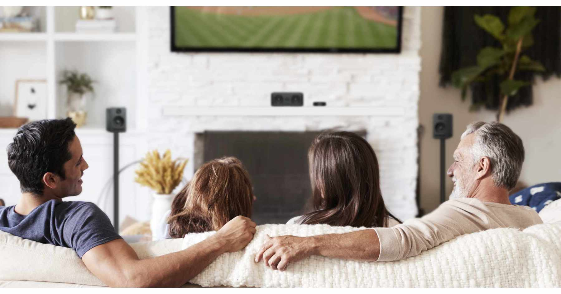 Two generations of family in a living room watching baseball and enjoying home cinema speakers