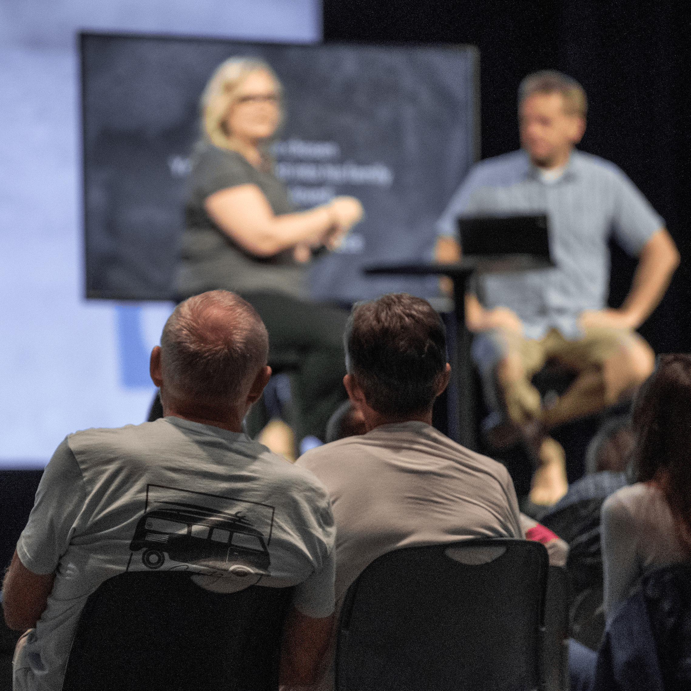 A couple watching a man and woman speaking from a stage with a screen in the background.