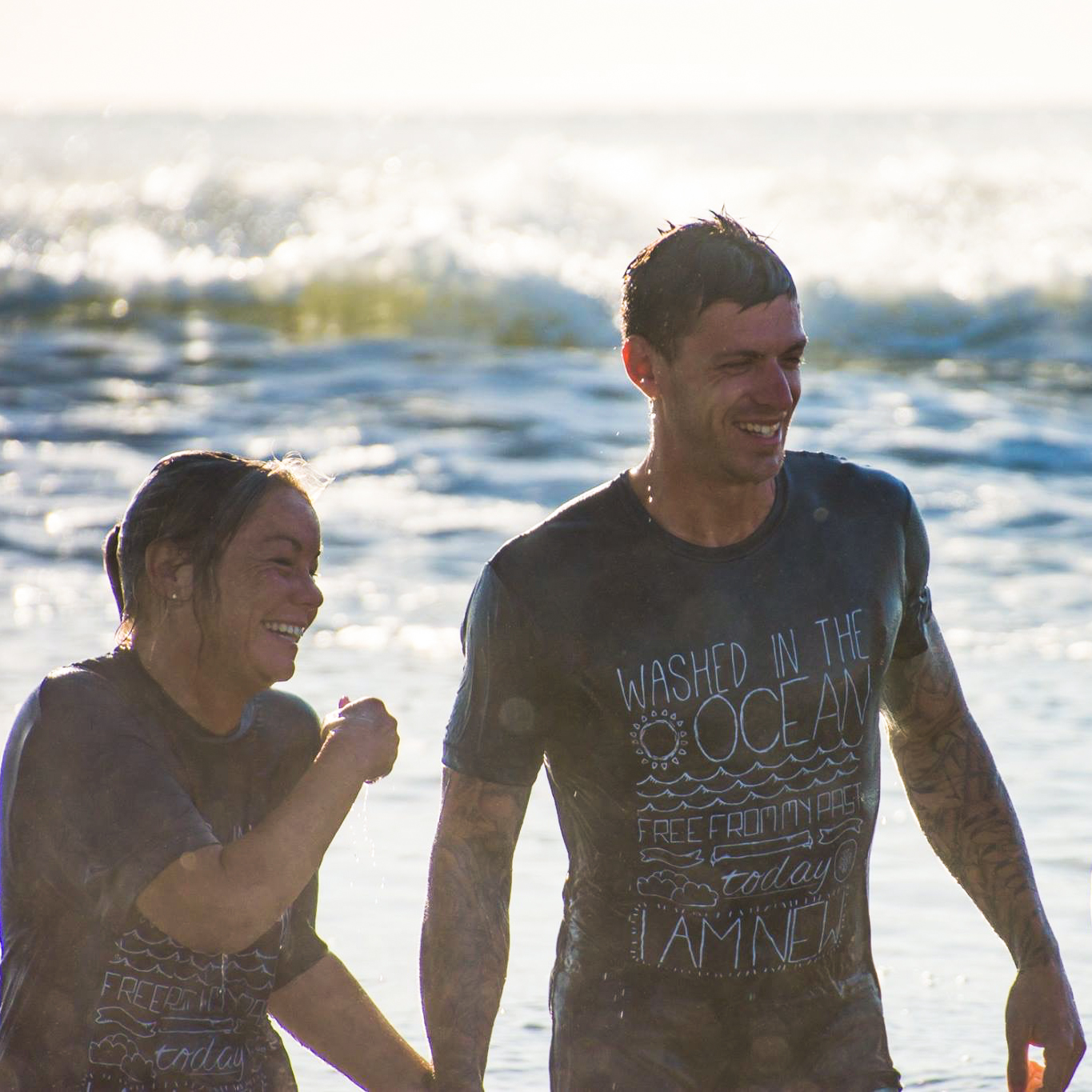 A young couple that has been baptized walking out of the ocean.
