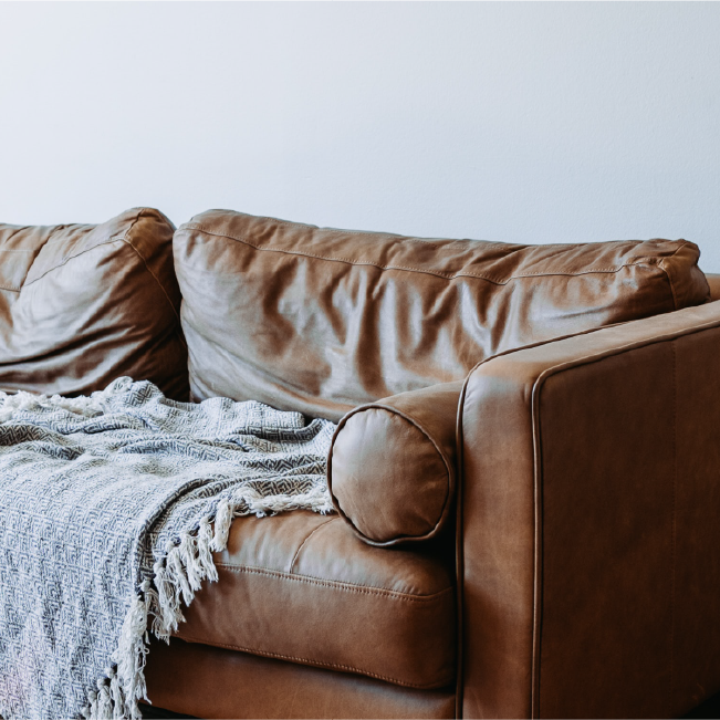 Brown leather couch in a living room with a light grey blanket sitting on it.