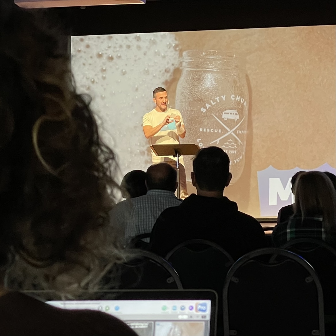 Msan speaking from stage with a screen behind him with a mason jar that reads Salty Church.