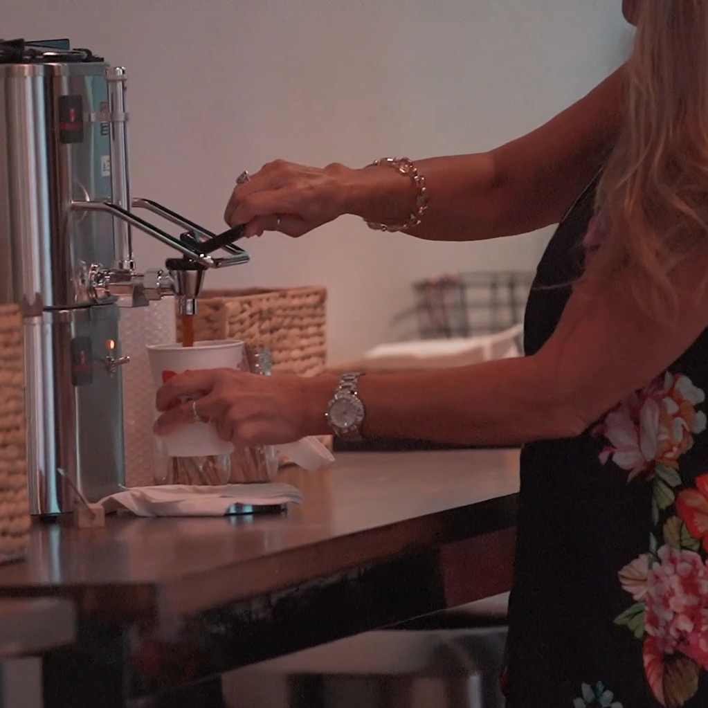Woman getting coffee out of a large carafe.