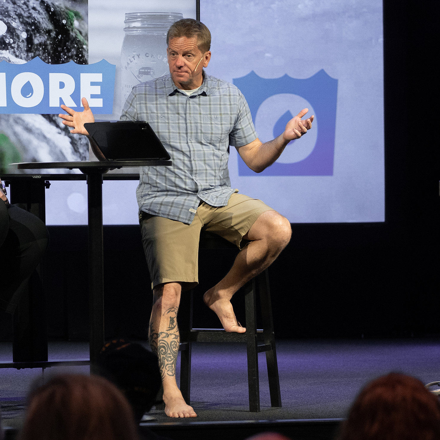 Man speaking from a stage sitting on a stool without shoes on.